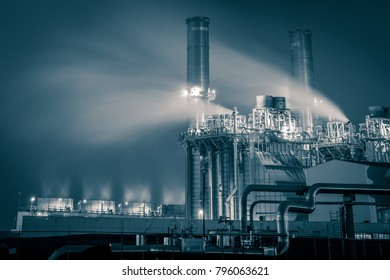 chemical plant or oil refinery at night with steamy creating long clouds in black and white with tones of blue