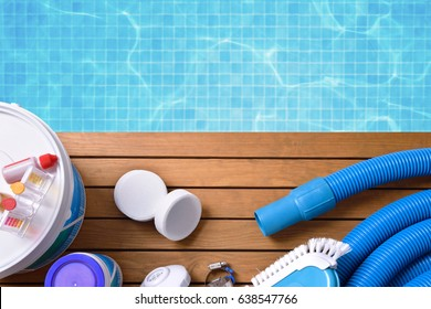 Chemical products and tools for the maintenance of the pool on wooden slats. Pool with water and blue mosaics background. Horizontal composition. Top view