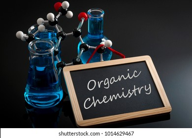 Chemical reaction, science class and STEM concept with a model of a molecule on chemistry glassware and flasks filled with blue liquid and a chalkboard with organic chemistry written on