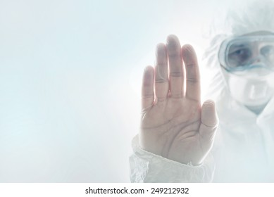 Chemical Scientist Gesturing Stop Sign with his Hand Raised in the Air, while wearing a protective clothing. Chemical disaster and pollution conceptual image with selective focus and shallow DOF.