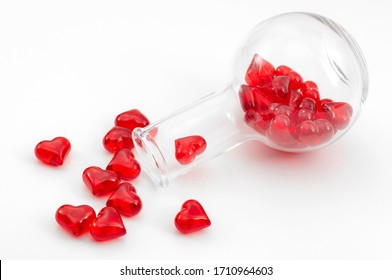 The chemicals of love and of the science of attraction concept with chemistry flask with glossy red heart falling out of it isolated on white background