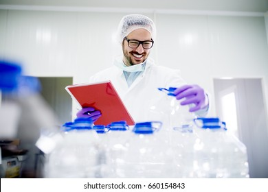 Chemist doing quality control of bottled water. Checking whether it meets all the required standards.