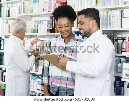 Chemist Explaining Prescription To Customer In Pharmacy