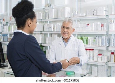 Chemist Giving Medicine To Female Customer