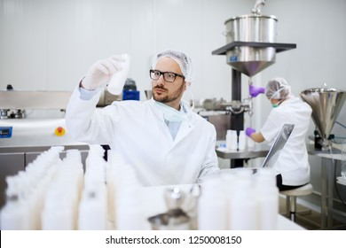 Chemist holding and looking at bottle with liquid soap while doing quality control. On desk bottles and laptop. In background his assistant pouring soap in bottles.