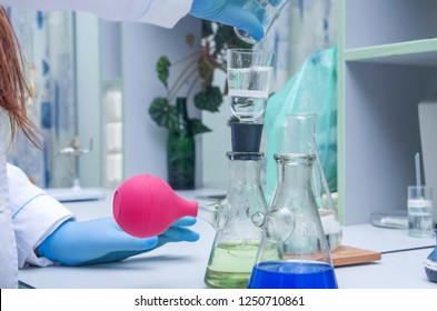 a chemist holds a glass test tube in his hand, overflows a liquid solution, conducts an analysis reaction using various reagent options using chemical production.