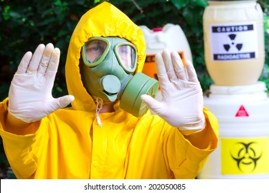 Chemist in protective clothing with gas mask gives a warning sign,photography