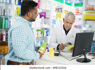 Chemist Scanning Product's Barcode While Customer Standing At Co
