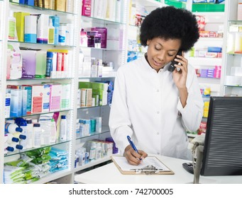 Chemist Writing On Clipboard While Using Cordless Phone