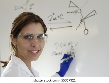 a chemist writing out equations on a white board for her students