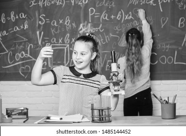 Chemistry classes. Girls classmates study chemistry. Microscope test tubes chemical reactions. Pupils at chalkboard chemistry lesson. Laboratory practice. Fascinating science. Educational experiment.