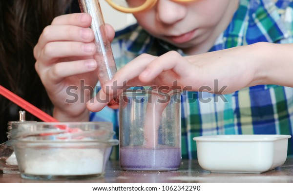 Chemistry experiments at home. The boy touches the liquid in the beaker with his finger.