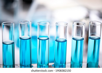 Chemistry laboratory glassware, science laboratory research and development concept, flask, beaker, and test tubes with blue liquid water sample test, scientific test tubes equipment