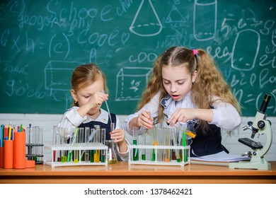 At chemistry lesson. Little school children holding test tubes at lesson. Small schoolgirls learning lesson at school. Having school lesson in science classroom.