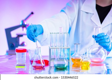 Chemistry. Mixing of chemical reagents. Chemist. A man works in a laboratory. Checking chemical reactions. Organic chemistry. Laboratory synthesis. A human mixes liquids. Career chemist.