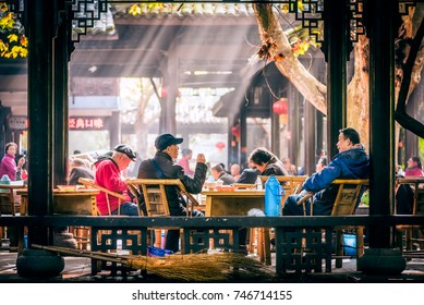 Chendu, China - Nov 1, 2017 : People sitting on bamboo chairs and having tea in People's park famous HeMing teahouse with sunrays in the background.