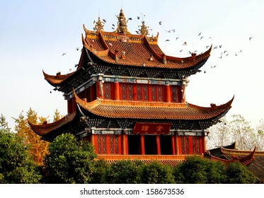 Chengdu, China:  A flock of doves circles the ornate bell tower with its flying eaved roofs at the Zhao Jue Buddhist Temple