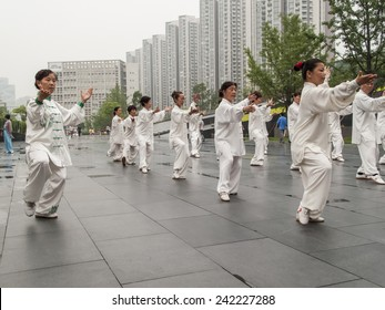 CHENGDU, CHINA - JUNE 4, 2012: Unidentified people practicing tai chi on the street of Chengdu, China. In China, tai chi is categorized under the Wudang grouping of Chinese martial arts