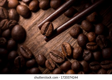 CHENGDU, CHINA - May 02, 2020: Closeup of a piece of coffee bean held by chopsticks, shot in dark food photography style and natural lighting.