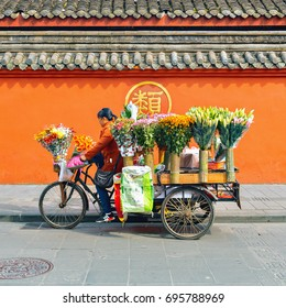 Chengdu, China - October 29, 2016: Woman drive the flower trade stand by the exterior of Wenshu monastery at sunny day time