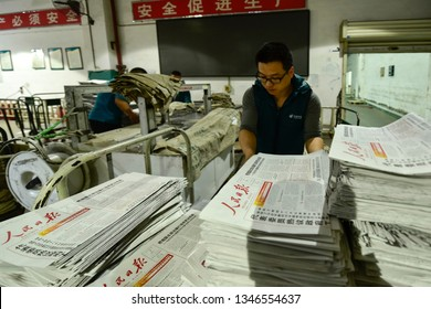 Chengdu, Sichuan / China - January 20 2019: Staff from a newspaper printing center is printing Ren Min Ri Bao, a newspaper supported by Chinese Communism Party. The process has been digitized.