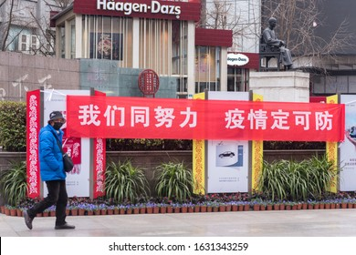 "Chengdu, Sichuan / China - January 30 2019: a person with masks walking by a sign that says "" if we work together we can control the coronavirus."""