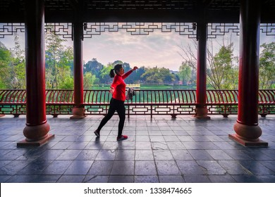 Chengdu, Sichuan / China - March 09 2019: a young woman is doing Tai Chi in Ren Min park. Tai Chi is very popular in China.