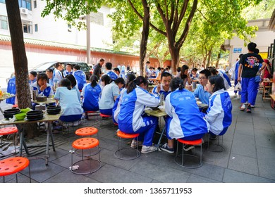 Chengdu, Sichuan / China - March 25 2019: students from Shi Shi Middle School enjoying lunch outside school on the street. Nearby restaurants put stools on the street for students.