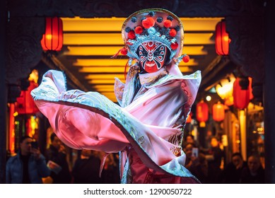 Chengdu, Sichuan Province, China - Jan 19, 2019: Chinese actress performs a public traditional face-changing art or bianlian onstage at Chunxifang Chunxilu covered street.