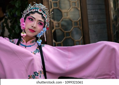 Chengdu, Sichuan Province, China - Nov 26, 2017 : Portrait of a young woman dressed in Sichuan Opera traditional costume in Kuan and Zhai alley touristic area.