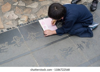 Chengdu, Sichuan province, China - Oct 2nd, 2017: Little boy copying chinese poetry in a textbook on the ground in HuanHuanXi public park