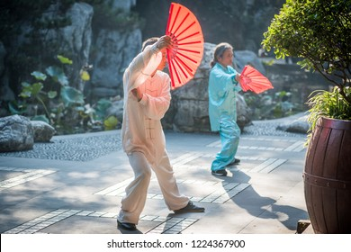 Chengdu, Sichuan province, China - Oct 31, 2018 : Man and woman practising Tai Chi with red fans in the morning in People's park.