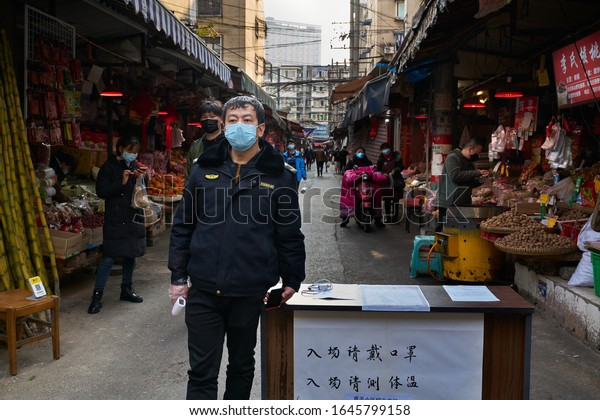 Chengdu/China-Feb.2020: Security guard with face mask outside a local seafood market for temperature screening during the ongoing outbreak of corona virus.