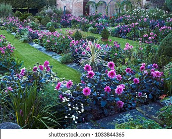 CHENIES MANOR TUDOR GARDEN AND PAVILION GALLERY, CHENIES, BUCKINGHAMSHIREM, ENGLAND, AUGUST 2014. The impressive sunken garden with a colourful display of Dahlias in late summer and the Tudor Pavilion