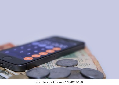 CHENNAI, INDIA - August 08, 2019: Close up view of Mobile Phone Calculate and new Indian rupees and coins on white background.
