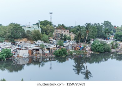 Chennai India July 28 2018 houses part of a slum and people seen living near the backwater seen with reflection on water and trees in between the houses