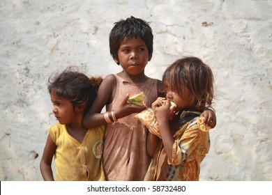 CHENNAI, INDIA - MAR 15: Poor Indian beggar girls on street  eating a piece of watermelon on March  15, 2009 in Chennai, India. Children of the early ages are often brought to the begging profession.