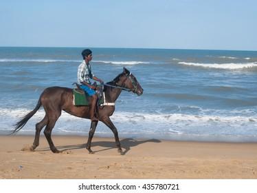 Chennai - June 11, 2012: A young man enjoys horse riding in Marina Beach, Chennai. The beach is the second longest beach in the world.