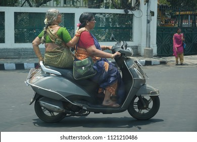 CHENNAI, TAMIL NADU, INDIA, MARCH 31, 2018: Two ladies in sari riding a scooter without helmet on a hot sunny day.