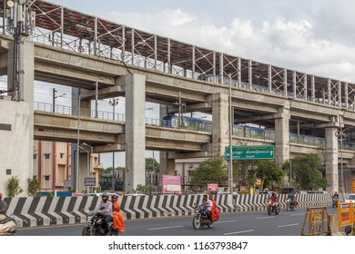 chennai,india,july 29 2018, national highway (known as kathipaara junction near guindy) with vehicles speeding on road on separate lanes with metro train moving on flyover.written in tamil language