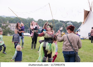 Chepstow, Wales – Aug 14: Bubblemen at Work – a green fairy creates giant bubbles for lots of children to play and pop 14 Aug 2015 at The Green Gathering Festival