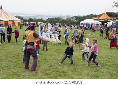 Chepstow, Wales – Aug 14: Bubblemen at Work – man creates giant bubbles for a crowd of children to children to play with and pop 14 Aug 2015 at The Green Gathering Festival