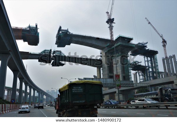CHERAS, KUALA LUMPUR- AUG 2019: SCENIC CITY VIEW OF ENORMOUS HIGHWAY BRIDGE IN CONSTRUCTION WITH THE HELP OF CRANE AND BUILDING INSTRUMENTS IN CHERAS