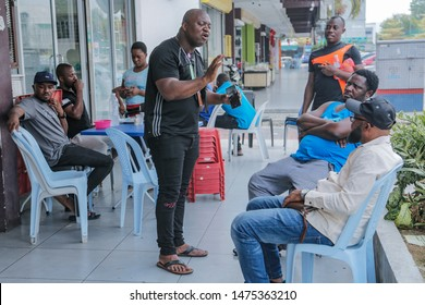 CHERAS, MALAYSIA - AUGUST 01, 2019. A number of Nigerian immigrants gather at the sidewalk of a shop as they talk to each other in Cheras, Kuala Lumpur.