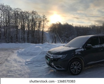 Cherepovets, Russia - March 07, 2019: Black car crossover Mitsubishi Outlander stands on the road with a dented left wing and a dent after an accident on the slip road
