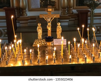 Cherepovets, Russia - March 30, 2019: Burning candles are in candlesticks for the dead in the Resurrection Parish Orthodox Church. Holy place. Memories of deceased loved ones