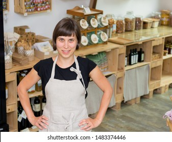 Cherfull young female shop owner posing in front of shelves full of healthy products.