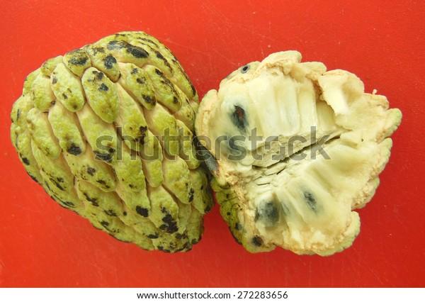 Cherimoya, soursop or guanabana cut open on orange cutting board