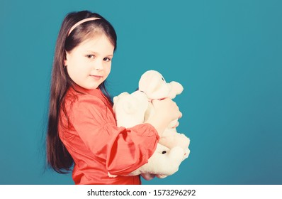 Cherishing memories of childhood. Childhood concept. Small girl smiling face with toys. Happy childhood. Little girl play with soft toy teddy bear. Lot of toys in her hands. Collecting toys hobby.