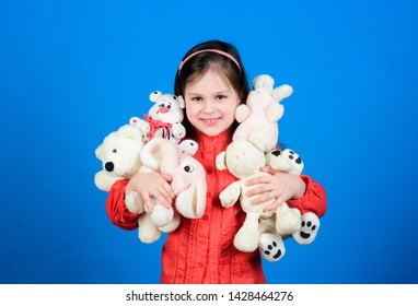 Cherishing memories of childhood. Small girl smiling face with toys. Happy childhood. Little girl play with soft toy teddy bear. Lot of toys in her hands. Childhood concept. Collecting toys hobby.